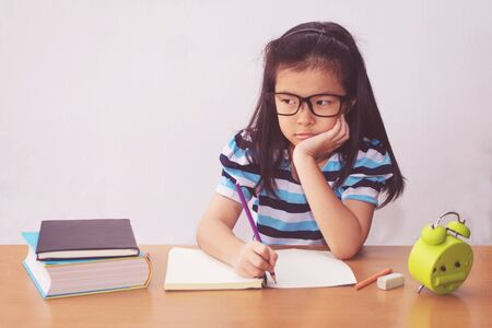 Bored and tired asian student girl doing homework