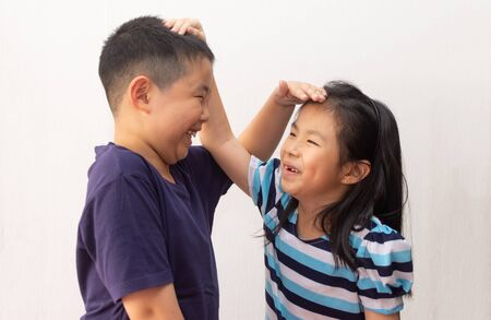 Happy little girl and boy measuring their height