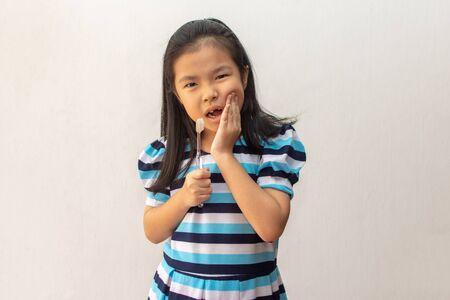 la ragazza asiatica ha mal di denti tenendo lo spazzolino da denti