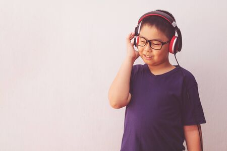Asia boy with headphones listening music.