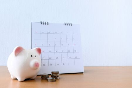 Calendar With Days and piggybank on wood table