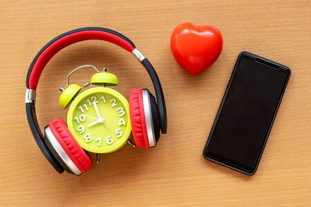 Headphones and alarm clock and smartphone and red heart on wooden desk. Musical concept