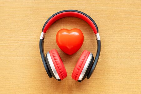 Headphones and red heart on wooden desk. Musical concept