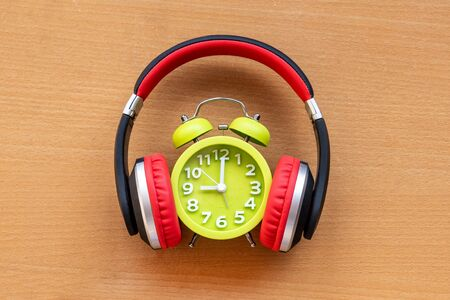 Headphones and alarm clock on wooden desk. Musical concept