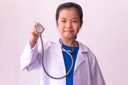 Asian girl playing doctor with stethoscope in hands. Imagens