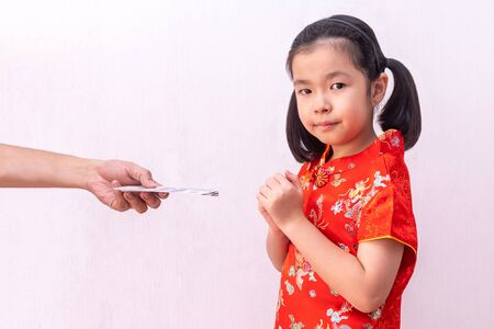 Asian girl wear cheongsam with gesture of congratulation, bring the hands together in greeting. in chinese new year Banque d'images