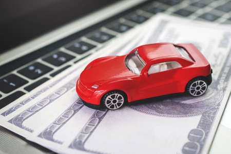 Car model, money and Notebook on wooden desk. shopping online and car payment by using laptop Imagens
