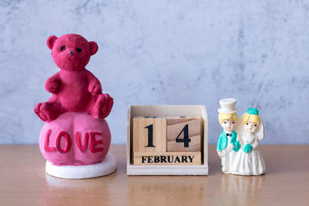 teddy bear and miniature Wedding couple with wooden calendar 14 february. Valentine s day