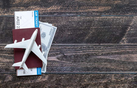 Toy airplane, Air Ticket, credit cards, dollars and passport on wooden table. Travel concept