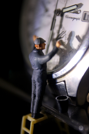 Miniature Worker Cleaning Watch Stock Photo