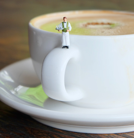 Miniature Waiter Serving a Cup of Hot Coffee