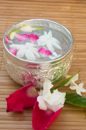 Water with jasmine and roses corolla in bowl on bamboo mat Stock Photo