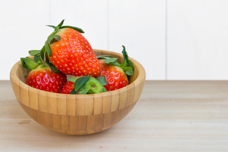 Fresh strawberries in wooden bowl on wooden textured table top. Stock Photo