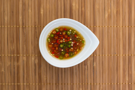 chilli sauce: Fish sauce and chili in a cup on bamboo stick straw mat Stock Photo