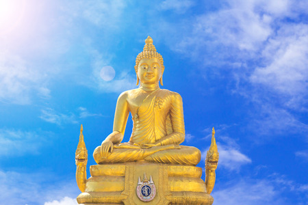 Golden Buddha statue on blue sky background