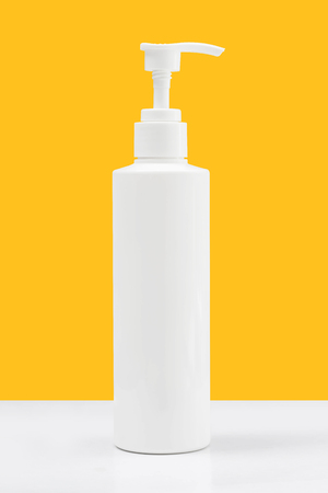 Gel, Foam or Liquid Soap Dispenser Pump White Plastic Bottle on yellow background with clipping path Stock Photo