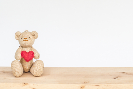 valentine s day teddy bear: Teddy bear holding heart on wood table isolated on white background, Love concept. Stock Photo