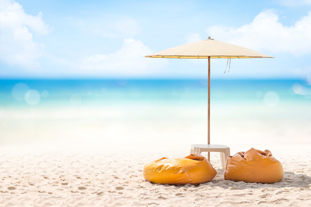 Two Yellow bean bags and outdoor umbrella on the sand beach.Summer holidays concept.