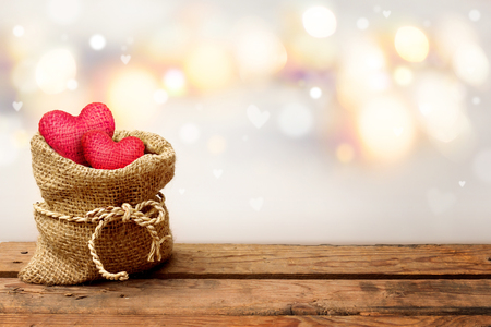 Two red heart in burlap sack on wooden table with bokeh background-Valentine day concept. Stock Photo