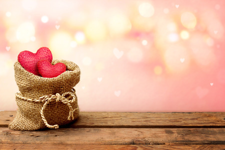 Two red heart in burlap sack on wooden table with pink bokeh background-Valentine day concept. Stock Photo