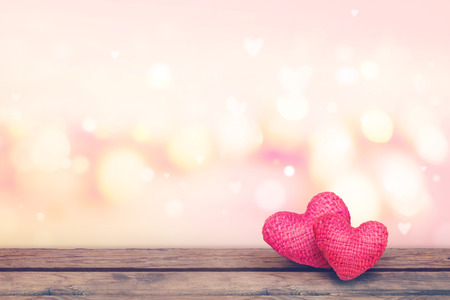 Soft focus red knitted hearts on wooden table with pink bekeh background-Valentine day concept.