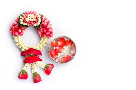 Thaise traditionele jasmijnslinger en water in kom met jasmijn en roze bloemblaadjes (gebruik voor eerbied aan ouder en de oude man in Songkran-festival in Thailand) geïsoleerd op witte achtergrond