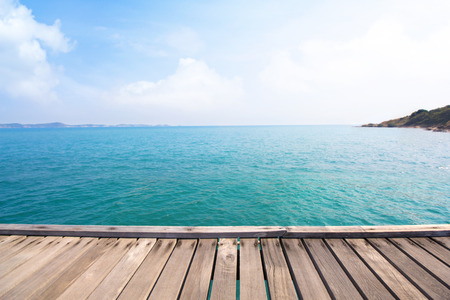 Wooden bridge over blue sea and tropical island beach background.