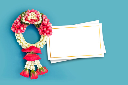 Thai traditional jasmine garland and blank white greeting card (Use for respect to parent and the old man in Songkran festival or Mothers day in Thailand) isolated on blue background Stock Photo
