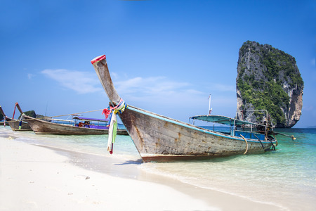 Longtail boat on white sand beach and landmark at Po-da island, Krabi Province, Andaman Sea, South of Thailand