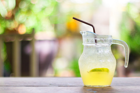 Refreshing summer cocktail-Honey lemon soda with lime slice in pitcher on wooden table with natural background. Stock Photo