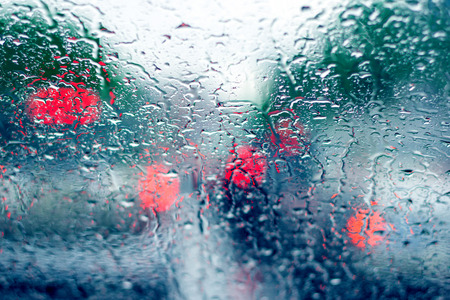 Traffic in rainy day with drops of rain. Street bokeh lights out of focus. Stock Photo
