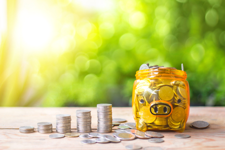 A transparent piggy bank with coins stack on wooden table with green bokeh background.Saving money concept