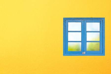 Closed blue wooden window on yellow wall background