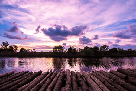 Wooden bridge with beautiful twilight sky after sunset in the evening in countryside near waterfront.
