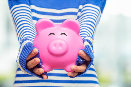 Woman holding a pink piggy bank, Saving and investment concept.