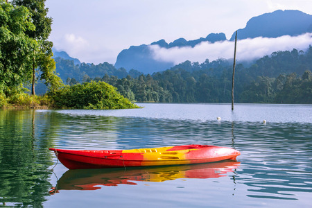 Yellow orange canoe or kayak with mountain lake view Stock Photo