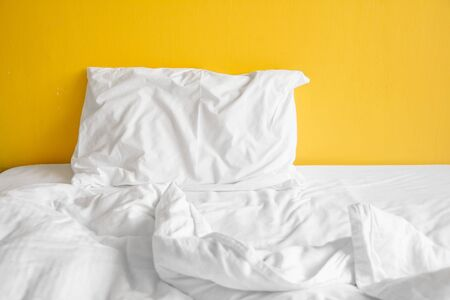 White pillow and with wrinkle messy blanket in bedroom on yellow wall Banco de Imagens