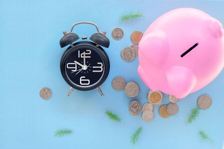 Top view of black alarm clock with pink piggy bank and coins on blue background-Saving concept