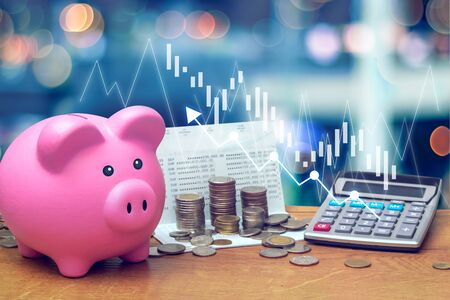 Coins stack on saving account book from bank with pink piggy bank and calculator on wooden table with candlestick chart suitable for finance and investment concept and blue bokeh background.