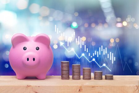 Pink piggy bank and coins stack on wooden table with candlestick chart suitable for finance and investment concept and blue bokeh background.