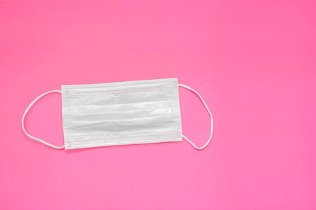 White medical mask isolated on pink background.Healthcare and medical concept. Banco de Imagens