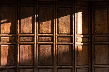 Sunset light and shadow on the old wooden folding door surface.