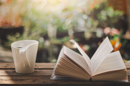 White cup of coffee and open book on the wooden table with morning light and blurred nature in the garden background.