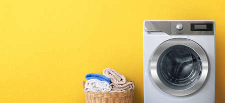 Washing machine with laundry near clean bath towels in wicker basket on yellow wall background-Copy space for text