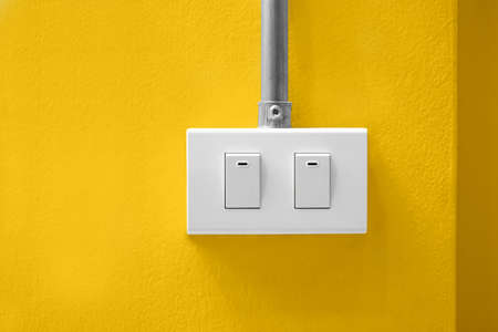White electrical light switch with pipeline on yellow wall background.