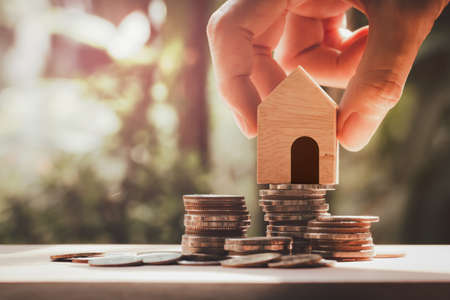 Hand holding house model put on stack coins, Savings for buy house , property, mortgage and real estate investment.Property real estate and financial concept.