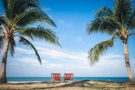 Two Beach Chairs between palm trees at the beach during a summer vacation-Vacation concept