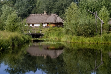 old ukrainian hut near the lake and the boat in forest photo