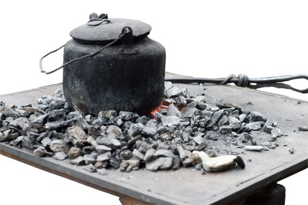 old dirty kettle on the burning hot coal photo