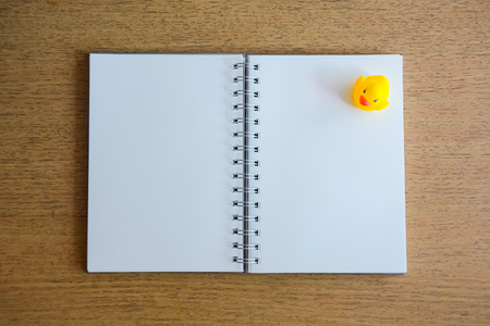 notebook and yellow duck on wood desk photo
